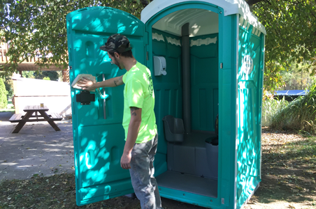 One of North Coast Sanitation's employees cleaning and sanitizing one of flushable portable toilets in preparation for delivery to a special event in Fairview, PA.